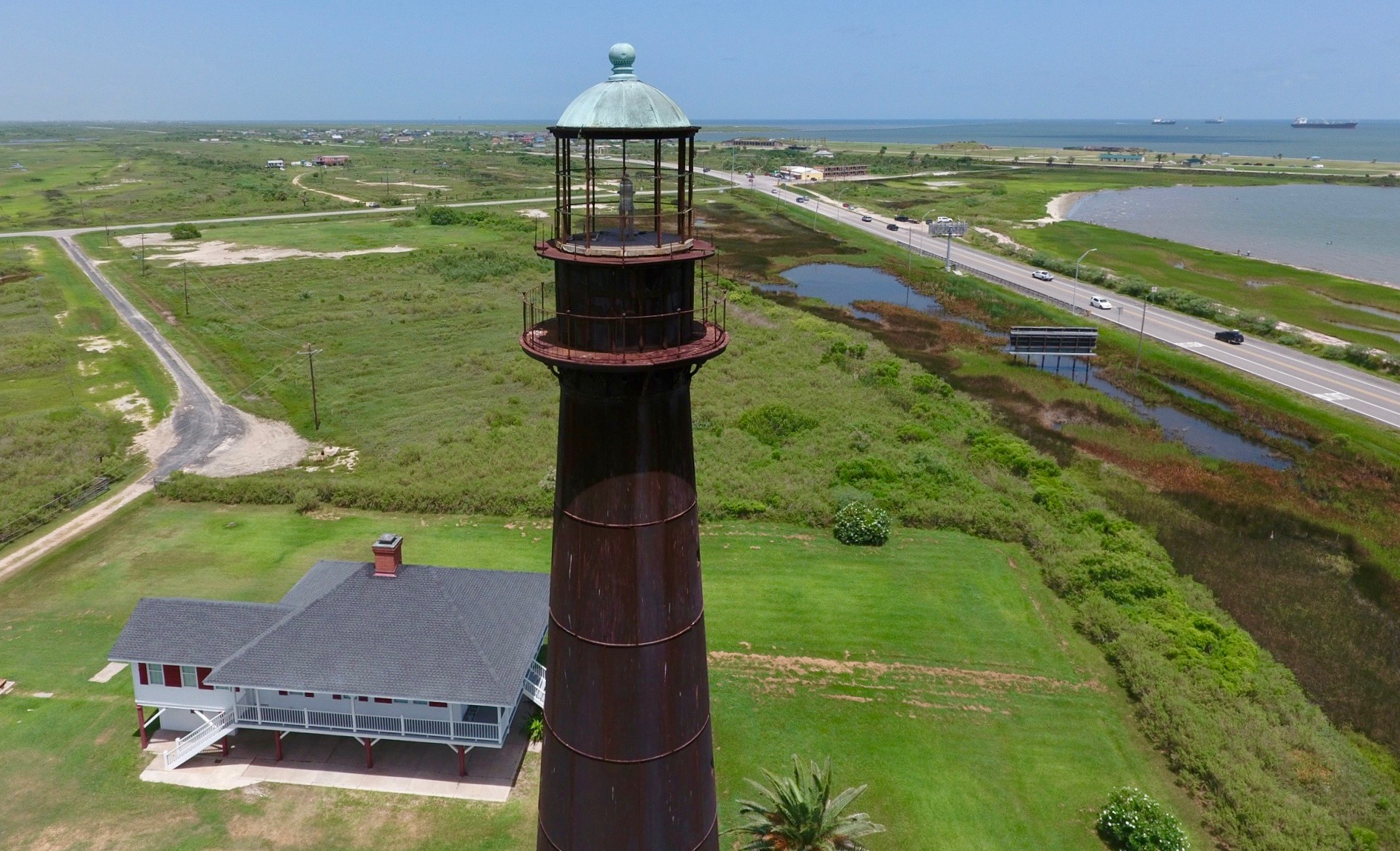 Aerial view of the Bolivar Peninsula Lighthouse in the daytime looking to Bolivar Peninsula. The lighthouse keeper's historic bungalow is below adjacent to Highway 85. The Gulf of Mexico is on the right and the green peninsula is center and left.