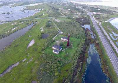 Drone image of the lighthouse, owner's property with three bungalows, and Highway 85. Marshes between the peninsula and mainland are on the left, beach and Gulf of Mexico are on the right.