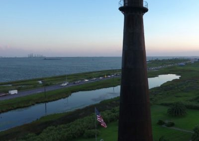 Bolivar Peninsula Lighthouse in the evening facing towards the Gulf of Mexico with Galveston Island on the horizon.